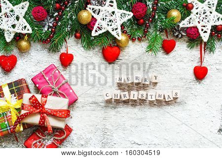 Merry Christmas. Christmas greeting card with fir tree decorations gift boxes and velvet hearts on rustic wooden background. top view