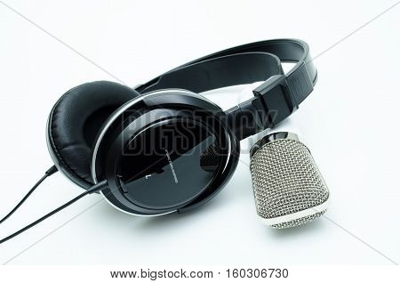 White microphone and black headphones on white background