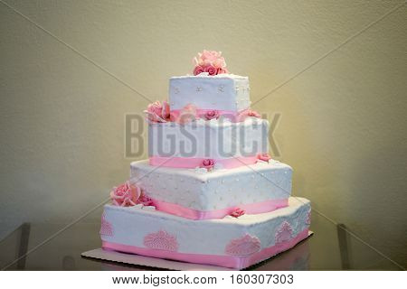 White storey wedding cake with pink edible marzipan flowers and pink decorative ribbon. Cake has four tiers square shape.