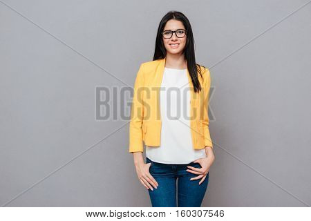 Image of joyful young woman wearing eyeglasses and dressed in yellow jacket posing over grey background. Look at camera.