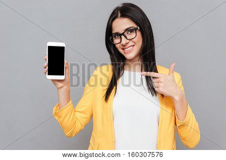 Photo of young woman wearing eyeglasses and dressed in yellow jacket pointing to phone display over grey background. Look at camera.