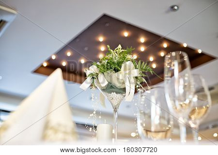 Wedding table decoration with white flower centerpiece taken in hotel restaurant before wedding reception spotlight on a ceiling at the background napkin and empty whine and champagne glasses.