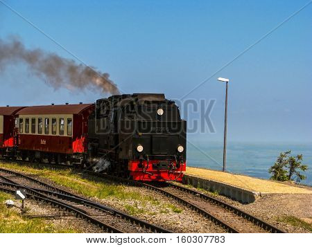 Black and red steam engine with passenger railway carriages, is standing on the platform