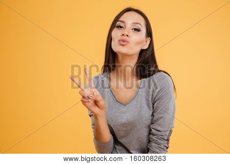 Pretty woman showing peace and send air kiss