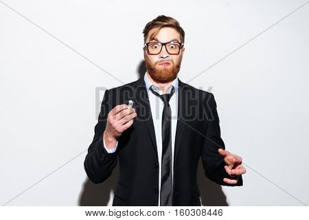 Young business man in glasses and black suit sniffing cocaine. Isolated gray background