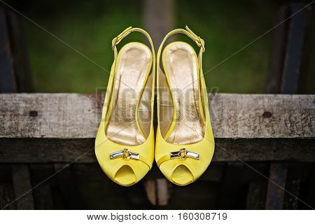 Yellow female satin open toe pumps detail. Photo is taken outdoor in rustical setting.
