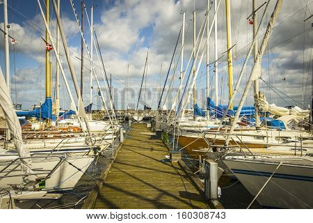 Several sailing boats are moored to the wharf with a mole on the back and with blue cloudy sky. Horizontal orientation.