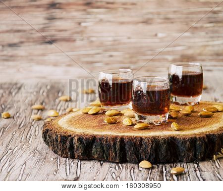Italian liqueur Amaretto in cups with almonds on a wooden table, selective focus