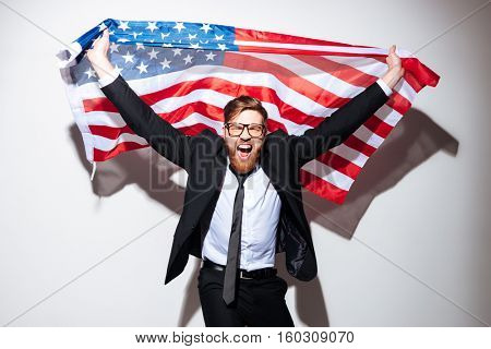 Happy bearded Business man holding USA flag in hands from the his back and looking at camera with open mouth. Isolated gray background