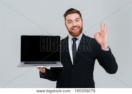 Happy bearded business man showing blank laptop screen and showing ok sign. Isolated gray background