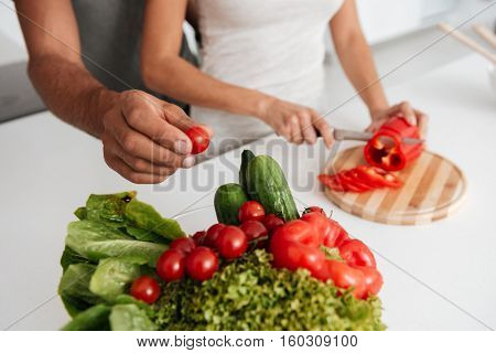 Cropped image of loving couple in the kitchen cooking. Man takes away the products.