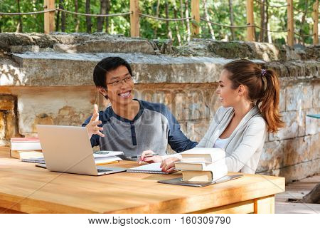 Happy young couple of students studying with laptop outdoors and laughing