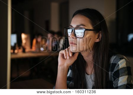 Serious businesswoman wearing glasses working late at night in office with computer. Looking at computer.