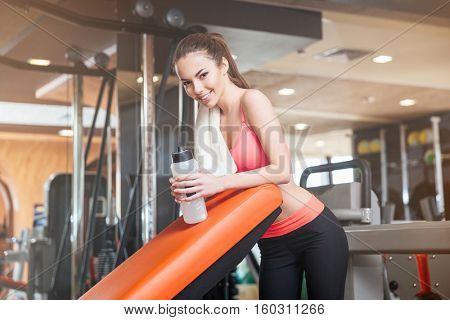 Portrait of happy beautiful young sportswoman with towel and bottle of water on training in gym