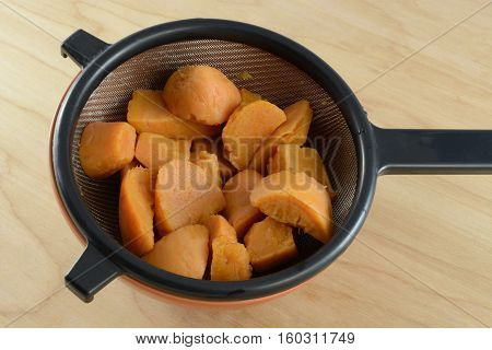 Rinsed canned yams draining in strainer in bowl on table