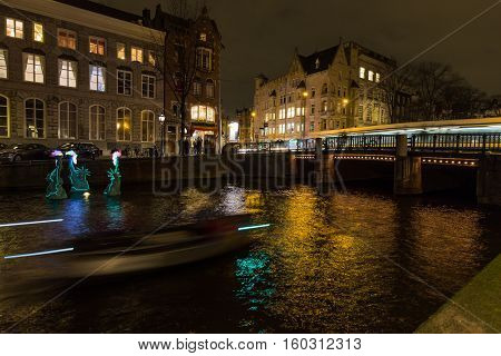 AMSTERDAM - DECEMBER 29, 2015: A boat and a tram pass by an Artwork entitled