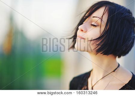 Young beautiful brunette woman eyes closed enjoying the bright warm day on blurred background close up
