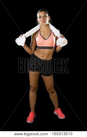 young attractive sexy latin sport woman posing with towel in fierce and badass face expression with fit slim body isolated on black background in healthy lifestyle and fitness concept