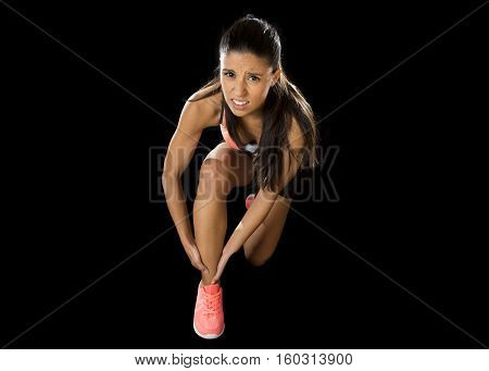 young attractive sport woman holding injured ankle suffering pain in ligaments injury or pulled muscle isolated on black background in fitness accident and body health care