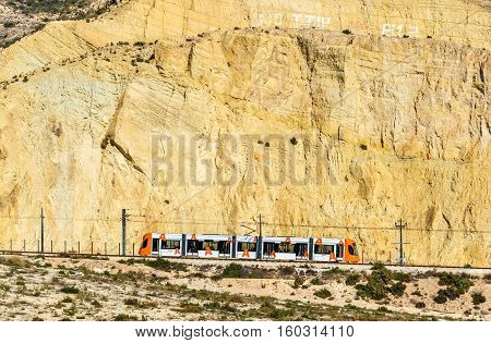 Alicante, Spain - October 30, 2016: Tram coming from Benidorm to Alicante near the Sierra Grossa Mountain. It is a narrow gauge railway, 1000 mm
