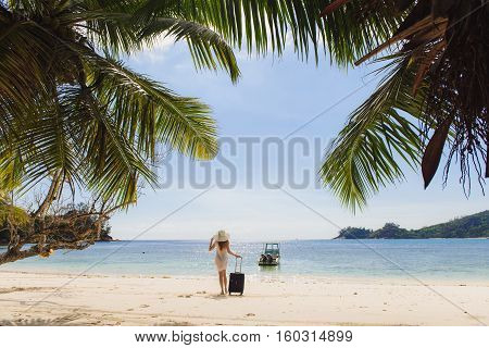 Young woman with hat and suitcase on the beach. Transparent clothes, bathing suit. Palm fronds framed photo.