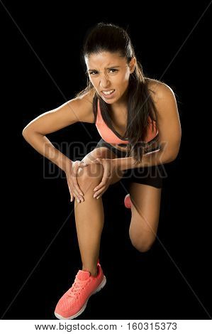 young attractive sport woman holding injured knee suffering pain in ligaments injury or pulled muscle isolated on black background in fitness accident and body health care