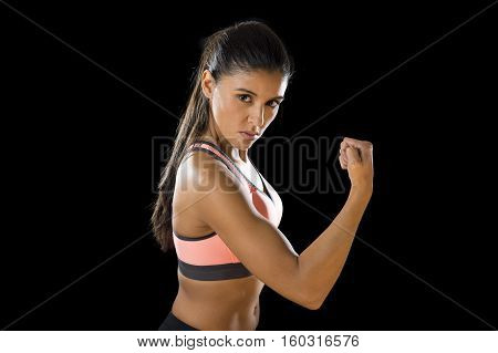 young attractive sexy latin sport woman posing in fierce and badass face expression with fit slim body isolated on black background in healthy lifestyle and fitness concept