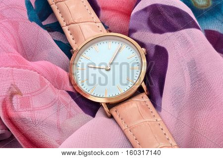 Classic pink wrist watch on colourful silk fabric background