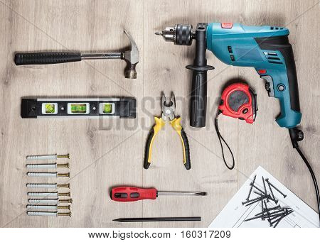 Set of construction tools to repair on a wooden surface: drill, hammer, pliers, self-tapping screws, roulette, construction level, drawing, construction pencil. Top view.