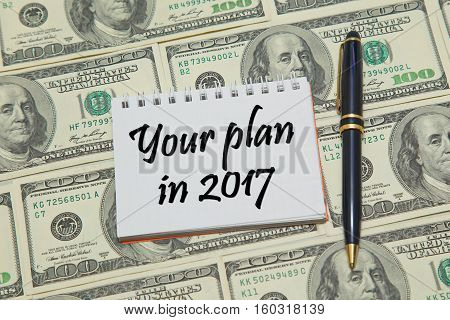 Notebook with text YOUR PLAN IN 2017 on dollar background