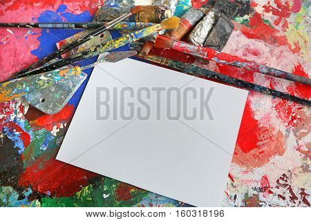 artist's palette with colored inks deposited randomly and art tools