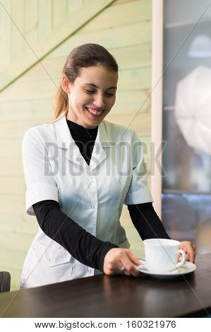Female nurse at a desk making coffee working in a modern office.