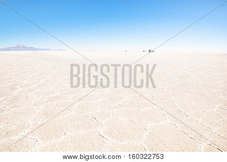 Unrecognizable people and off road vehicle on the horizon of Salar De Uyuni - World famous nature wonder destination in Bolivia - Travel and wanderlust concept in South American exclusive location