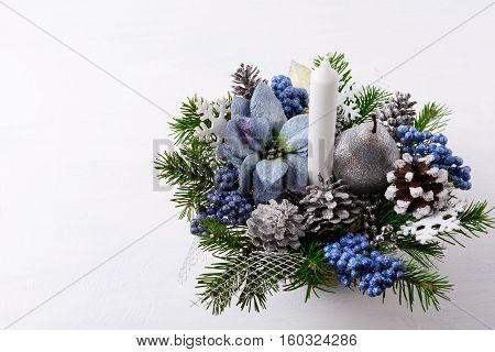 Christmas background with candle and blue silk poinsettias. Artificial Christmas flower arrangement with pine cones and fir branches. Christmas table centerpiece. Copy space.