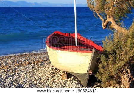 A beautiful old weathered wooden fishing boat on a pebble beach