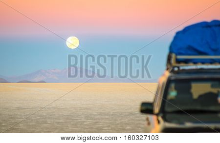 Full moon sunset with off road jeep vehicle on Salar De Uyuni - World famous nature wonder place in Bolivia - Travel and wanderlust concept in South American exclusive destination - Focus on infinity