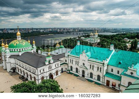 view of yard in Kyiv Pechersk Lavra and Kyiv cityscape from bell tower