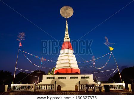 Moon on night sky over pinnacle white pagoda at Rayong Thailand.