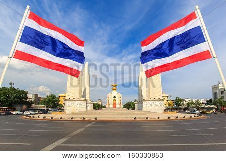Democracy monument with blue sky and thai flag foreground in sunshine day Bangkok Thailand