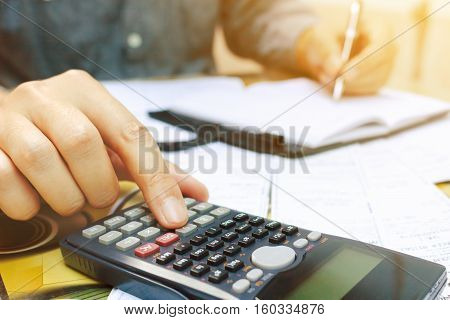 Close up man using calculator and writing make note in home office.