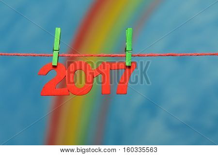 Red 2017 New Year's Eve numbers with a colorful rainbow and blue sky background sky to illustrate the concept of new beginnings and resolutions.