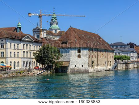Solothurn, Switzerland - 10 July, 2016: historic buildings along the Aare river, towers of the St. Ursus Cathedral in the background. The city of Solothurn is the capital of the Swiss Canton of Solothurn.
