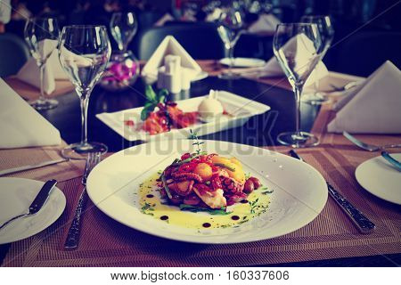 Seafood appetizer and tasty dessert on restaurant table, toned image
