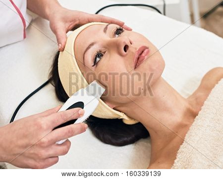 Young pretty woman receiving treatments in beauty salons. Ultrasonic cleaning procedure. Hardware cosmetology. ultrasonic peeling