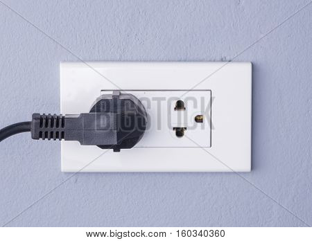 Black Cable Plugged In A White Electric Outlet Mounted On Gray Wall
