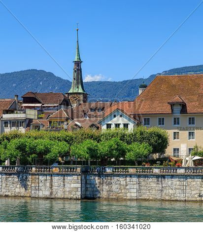 Solothurn, Switzerland - 10 July, 2016: historic buildings along the Aare river, mountains in the background. The city of Solothurn is the capital of the Swiss Canton of Solothurn and is also the only municipality of the district of the same name.