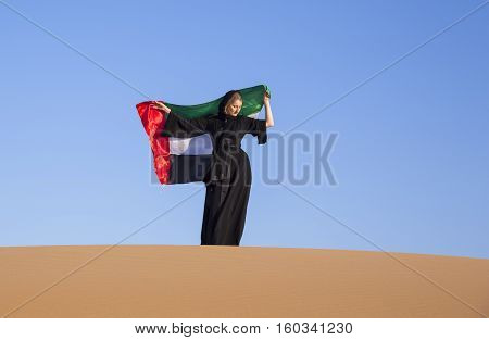 young woman in abaya with UAE flag in a desert