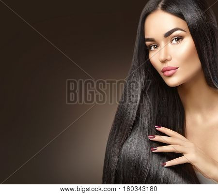 Beautiful long Hair. Beauty woman with luxurious straight black hair on dark background. Beautiful brunette Model girl touching Healthy Hair. Lady with long smooth shiny straight hair. Hairstyle, cure