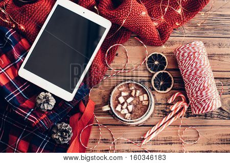 Weekend homely scene. Warm knit blanket and cup of hot cocoa with marshmallows. Christmas lollipop, led lights string and other holiday decor. Tablet pc with blank screen, watching winter movies.