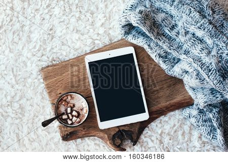Winter homely scene, scandinavian style. Warm knit sweater, tablet pc with blank screen and cup of sweet cocoa with marshmallows on wooden tray in bed. Lazy cold weekend.